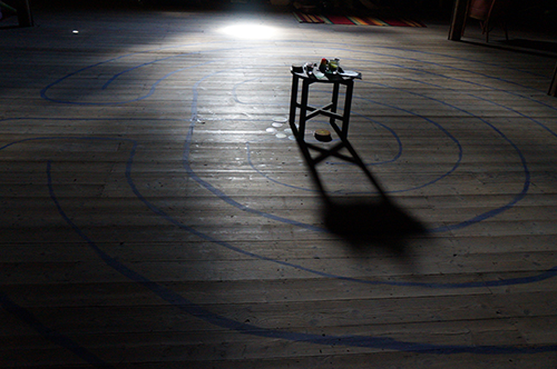 dark room with a crack of light, stool at centre of image, labyrinth painted on the floor