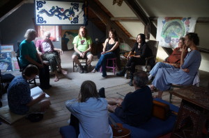 A group sit in a circle listening to a workshop facilitator