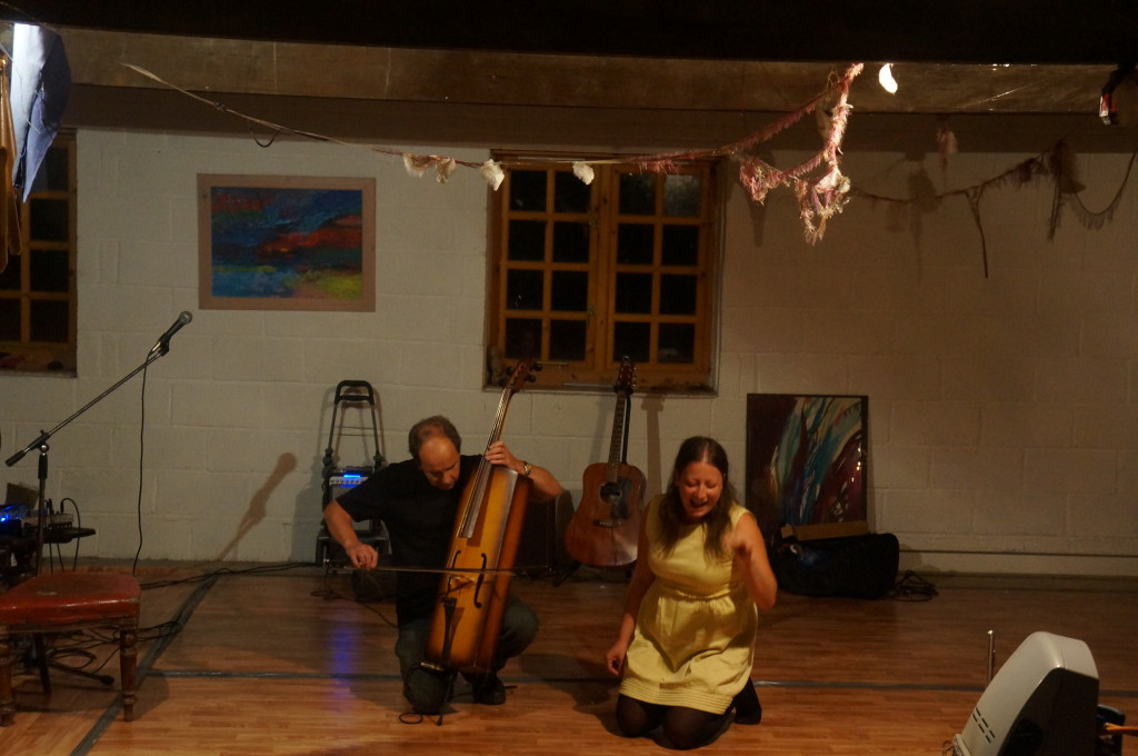 A man kneels playing a cello, a woman kneels wailing melodramatically
