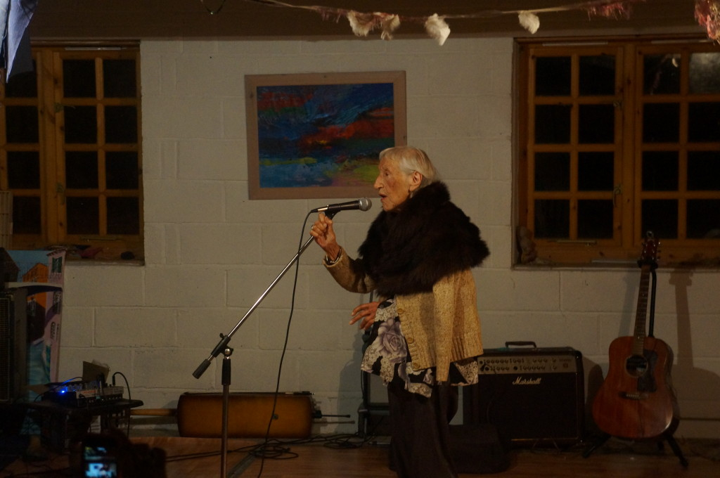 A woman performs alone, speaking into a microphone
