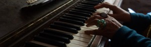 close up of hands playing at piano