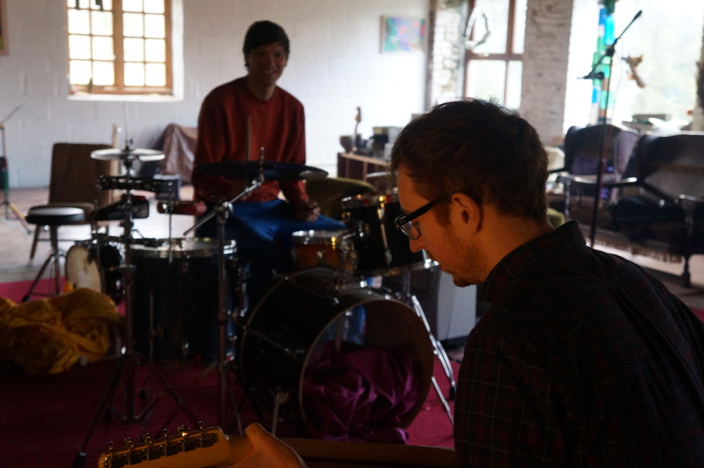 two men work on a song on guitar and drums