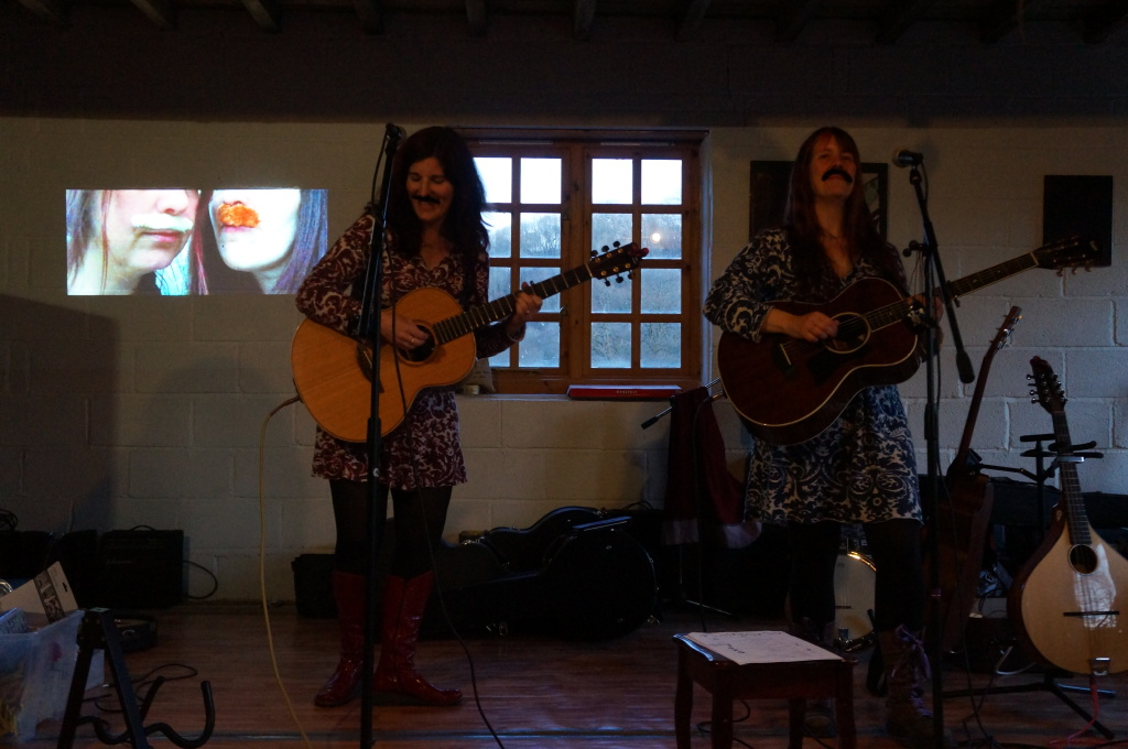 Two women wearing fake moustaches perform in the mill, they are singing and playing guitars.