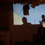 Two people perform music, a film of seagulls flying is projected in the background